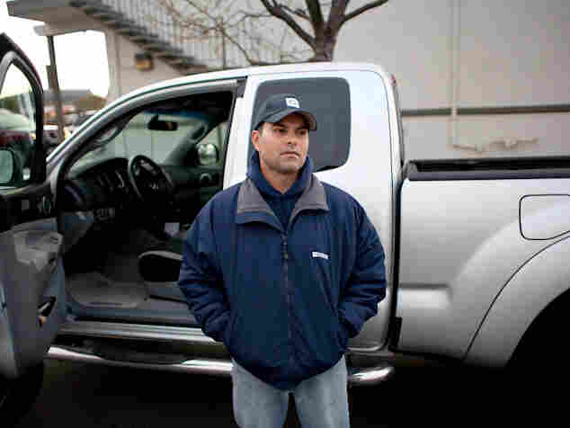 Laidoff worker Johnny Rowe stands in front of a Toyota truck built at the facility.