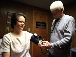 Physician assistant Tom Harward takes a patient's blood pressure.