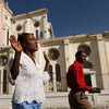 Haitians pray as they walk past the ruins of the National Cathedral.