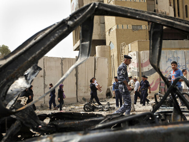 Iraqis inspect the site of a car bomb attack Sunday near the Iranian Embassy in Baghdad.