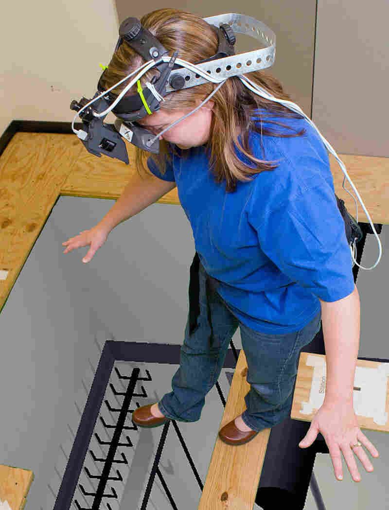 A student in an augmented environments lab at Georgia Tech stands over a simulated three-story pit.