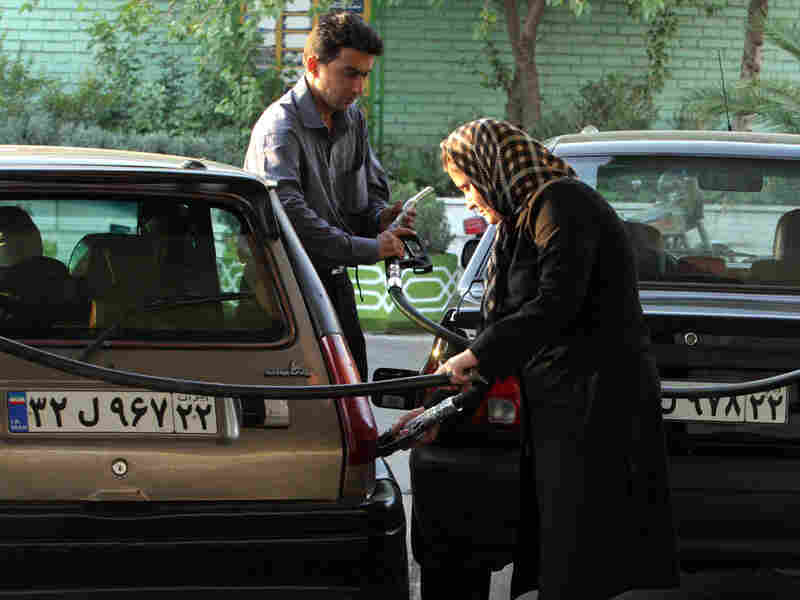 A woman and a man gas up their vehicles at a station in Tehran in 2007.