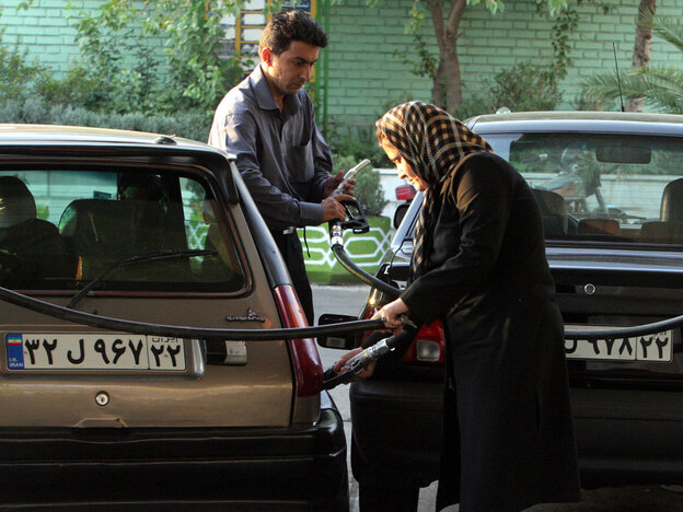 An woman and a man gas up their vehicles at a station in Tehran in 2007. Iran's economic problems are linked to its extensive use of subsidies — billions of dollars a year — to keep basic necessities such as gasoline below their true market value.