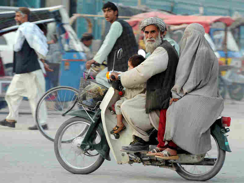 Man rides motorcycle in Kandahar city, November 2009