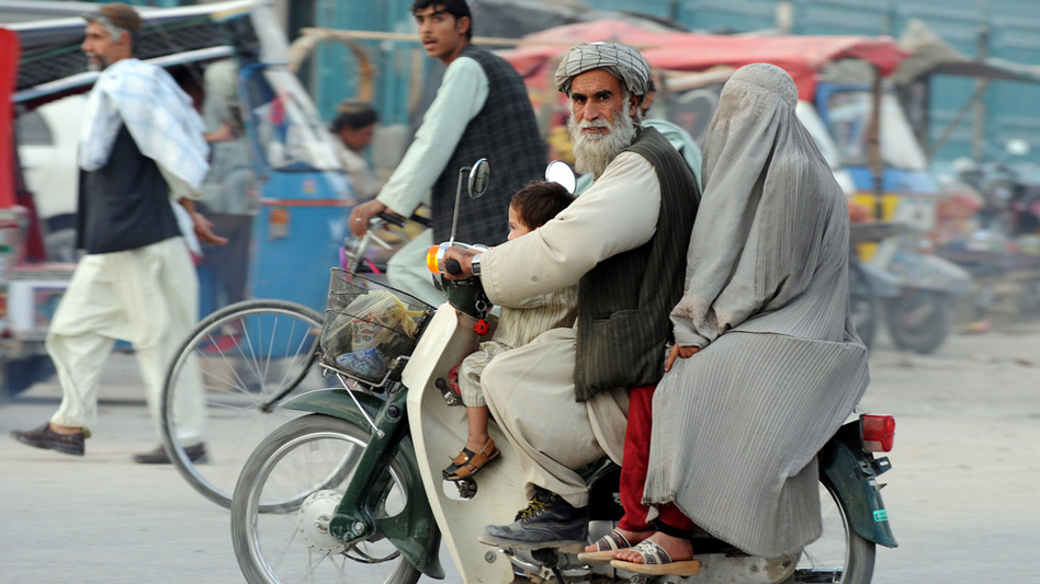 An Afghan man rides on a motorcycle with his family on a street in Kandahar city in November 2009. Many in Kandahar blame Western forces and Afghan officials — not the Taliban — for growing violence in the area during the past few years. Locals are nervous about the military offensive against the Taliban this summer.