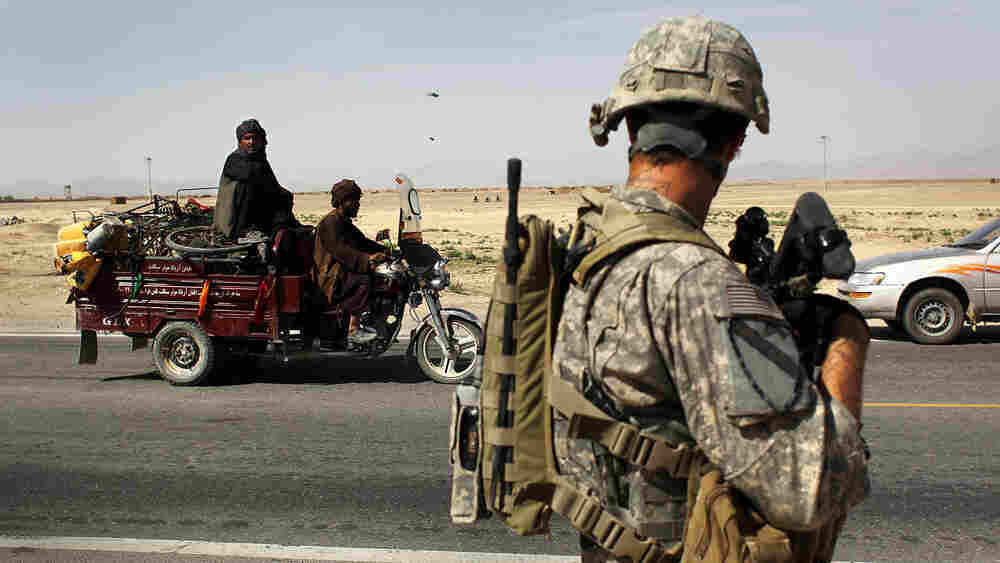 Motorists pass a U.S. soldier on patrol at Howz-e-Madad in Afghanistan.