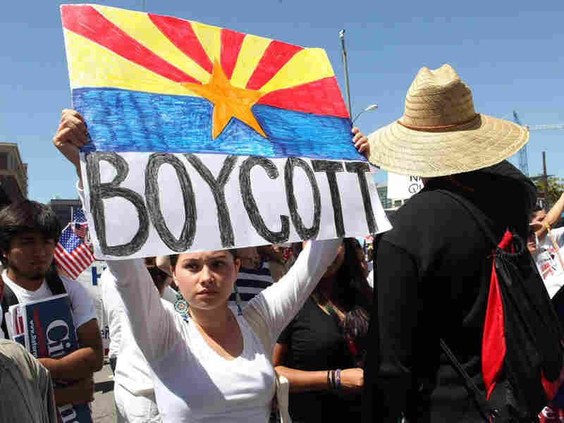 A woman holds a sign that says 'Boycott.'