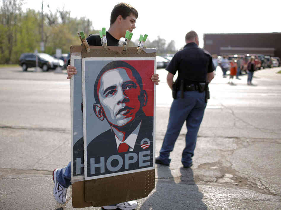 A vendor carries Barack Obama posters.