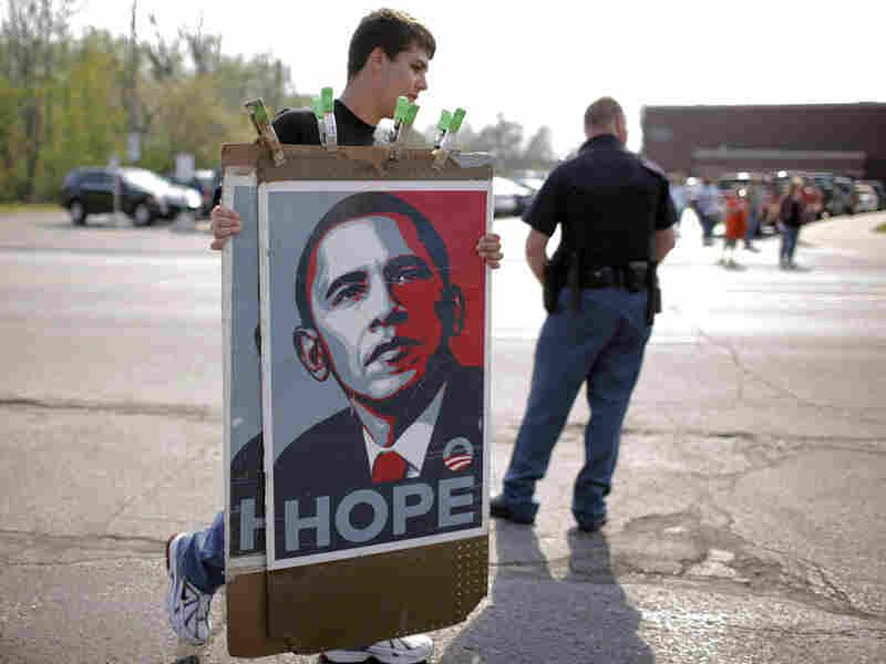 A vendor carries Barack Obama posters.
