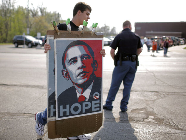 A vendor carries the iconic blue and red Obama posters to a town hall-style meeting the now president held in 2008.