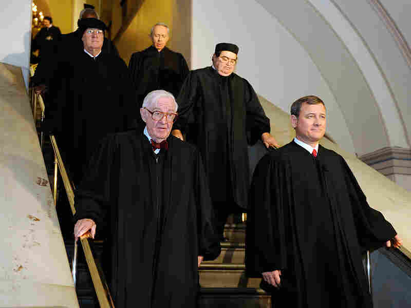 Supreme Court Justice John Paul Stevens and Chief Justice John Roberts walk with other justices.