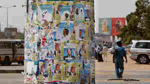 A Sudanese policeman patrols a street next to a pole covered in election posters in Khartoum, Sudan.