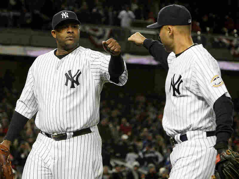 CC Sabathia of the New York Yankees is congratulated by Derek Jeter during Game One of the ALCS.