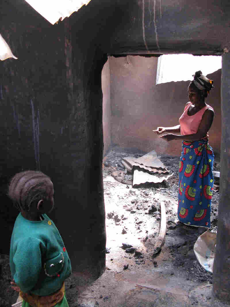 Victoria Yohanna and her 5-year-old daughter stand in the burned-out shell of their home.