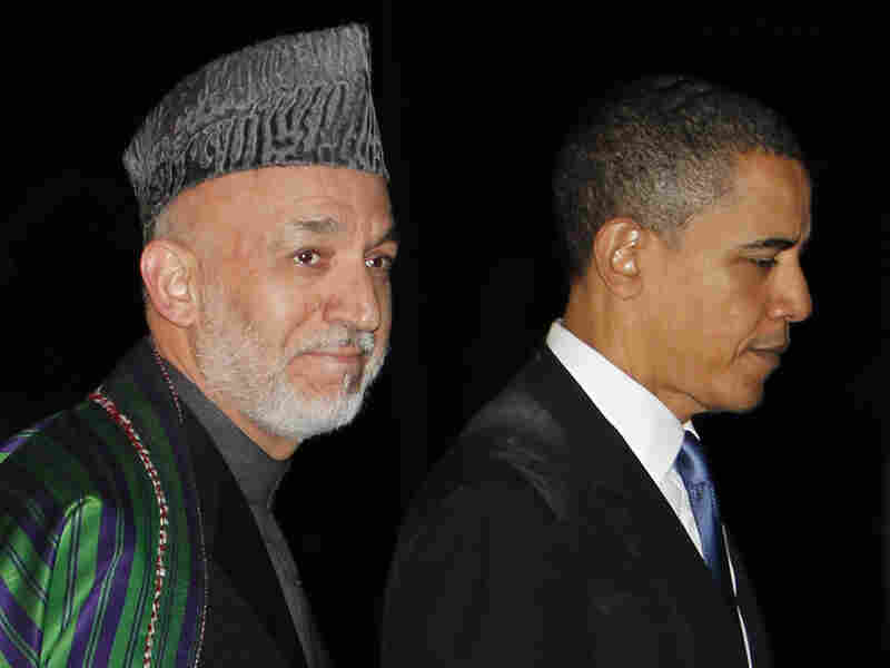 President Obama (right) walks with Afghan President Hamid Karzai