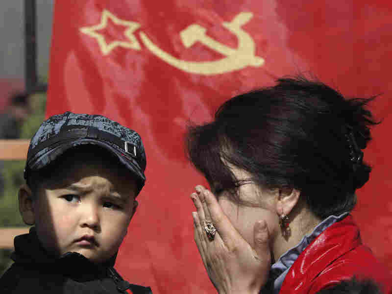Kyrgyz woman and boy in Bishkek, the capital, mourn protest victims