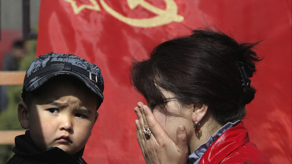 With a former Soviet Union flag in the background, a Kyrgyz woman, with her son, mourns victims of this week's violent protests. She was among the thousands of grieving and defiant citizens of Kyrgyzstan who gathered in the main square of Bishkek, the Kyrgyz capital, April 9, 2010, after two days of clashes forced President Kurmanbek Bakiyev to flee.