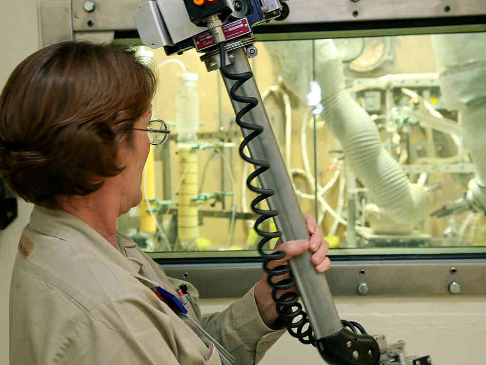 An employee works with a mechanical arm to manipulate items inside the hot cell.