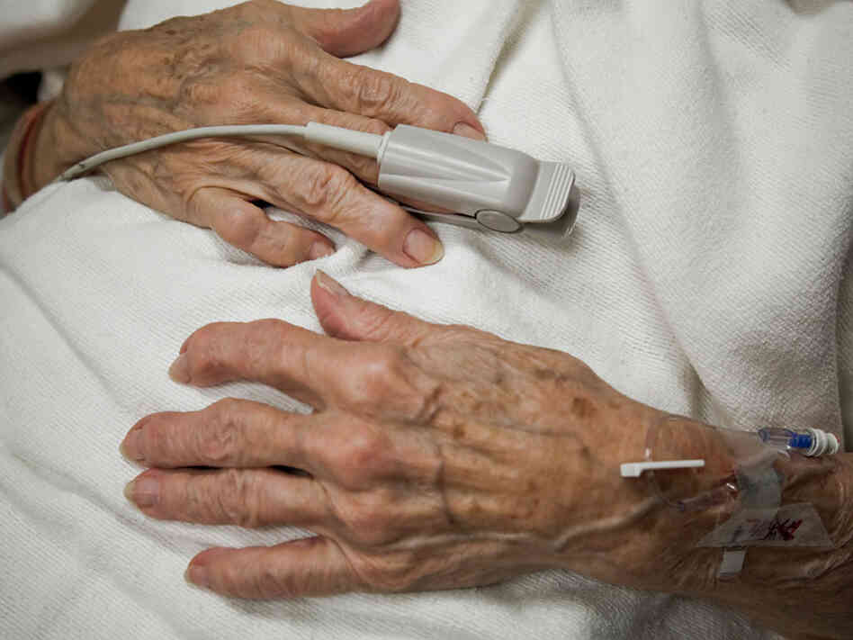 An older woman's hands on her lap as she lies in hospital bed.