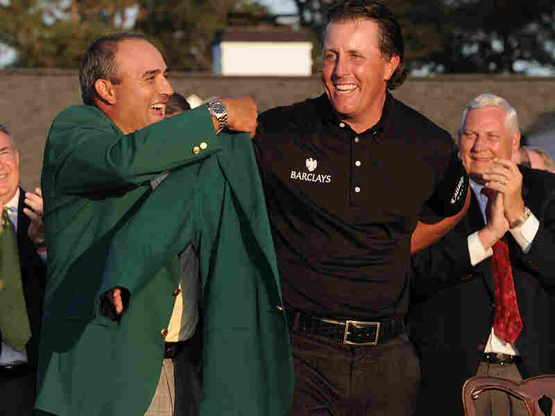 Phil Mickelson is presented with the green winner's jacket at the 2010 Masters Golf Tournament.