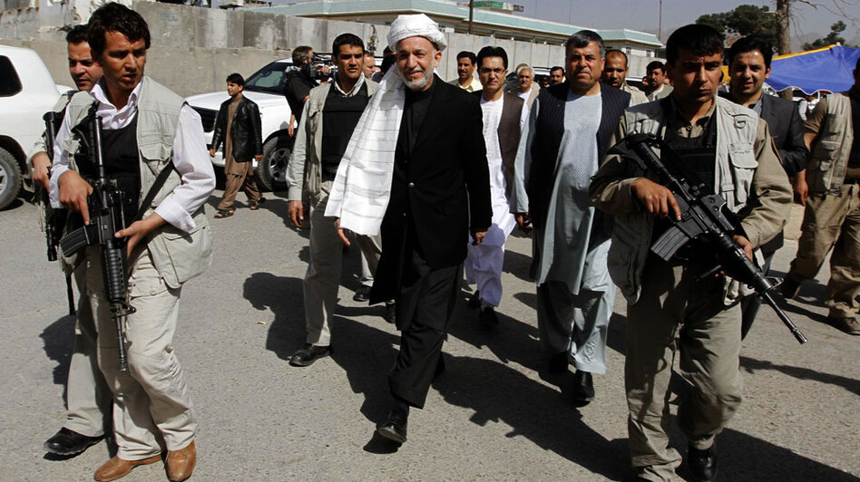Afghan President Hamid Karzai (center), surrounded by bodyguards, walks through Kandahar city, south of Kabul, earlier this month. The purpose of the president's visit was to consult with and seek the support of locals for an upcoming U.S. and NATO military campaign there to drive out the Taliban. But the operation is meeting resistance.