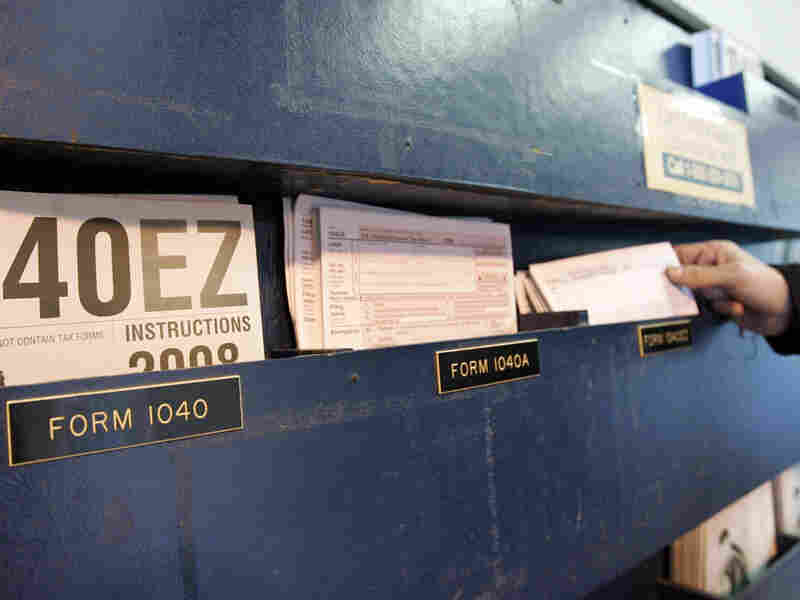 A man picks up federal tax Form 1040 at a post office.