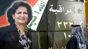 Man looks at poster of Iraqi woman candidate in March elections