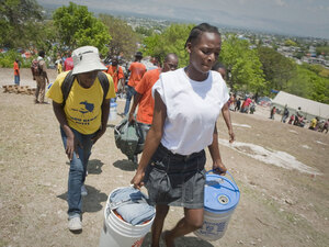 A woman at the Petionville camp carries her belongings as she prepares to relocate to Corail-Cessele