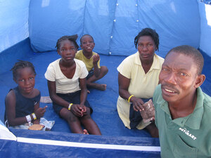 Louis Sainte Claudelle and his family in their tent at Corail-Cesselesse