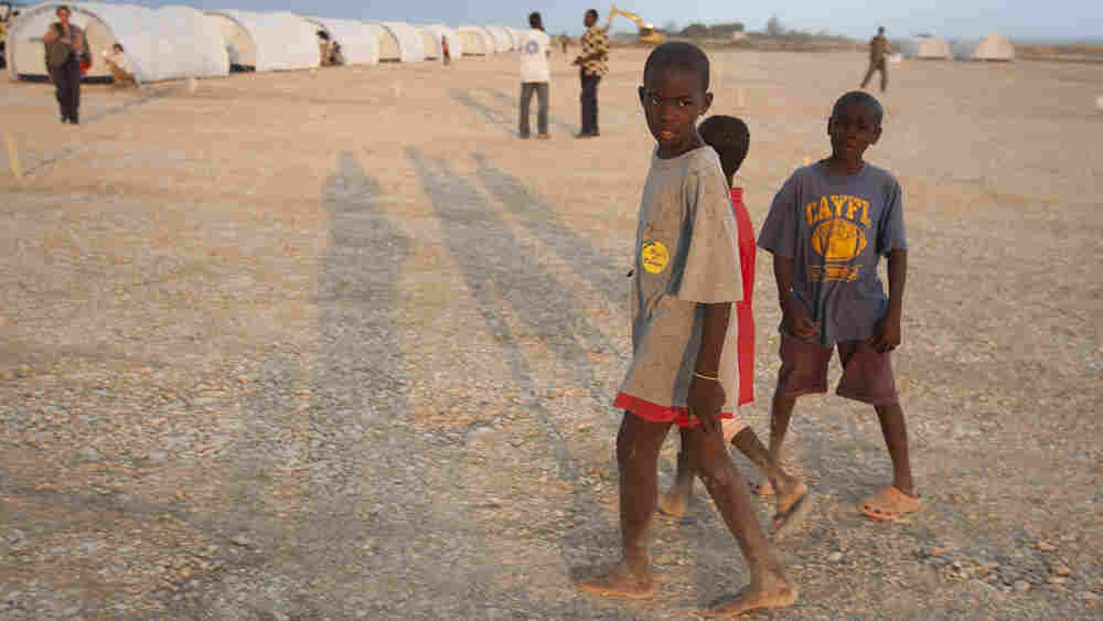 Children walk through their new home at a camp in Corail-Cesselesse, Haiti.