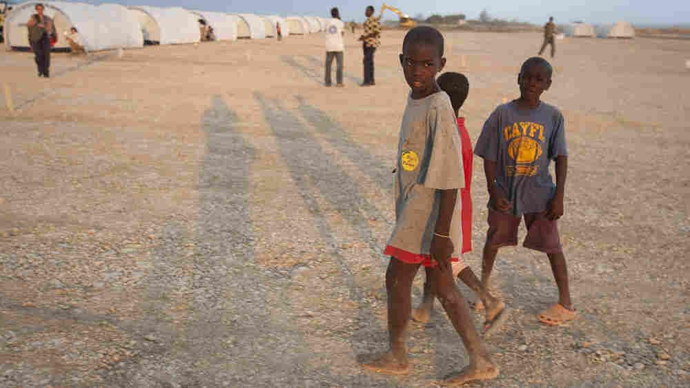 Children walk through their new home at a camp in Corail-Cesselesse, Haiti.