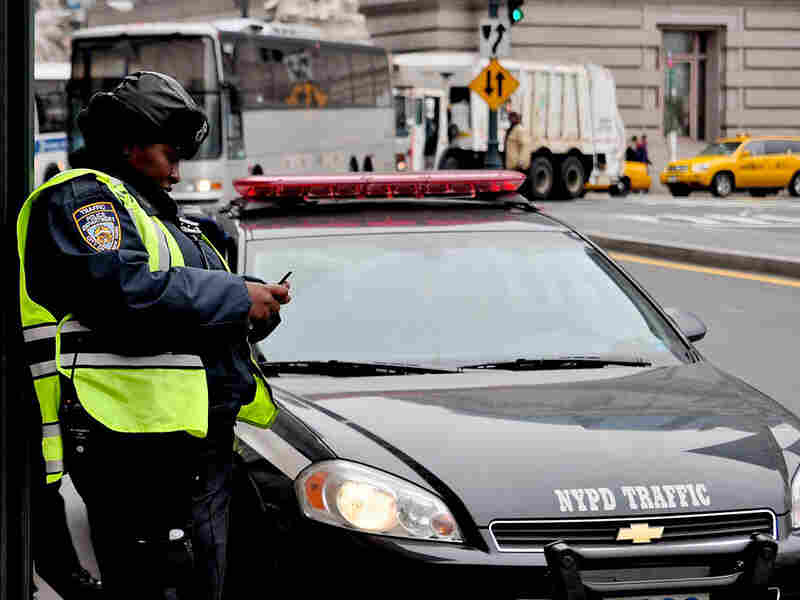 An NYPD officer uses a phone to send text messages on a New York sidewalk.