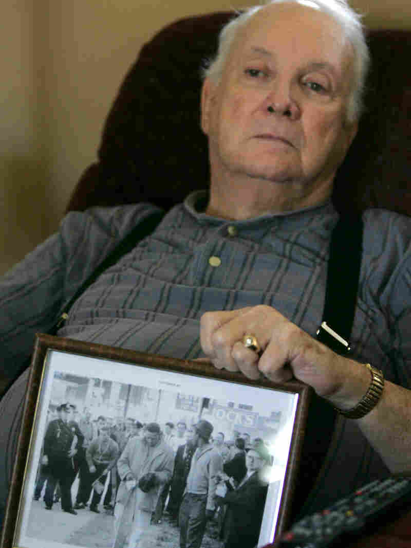 Elwin Wilson holds a photo of the mob he participated in in 1960.
