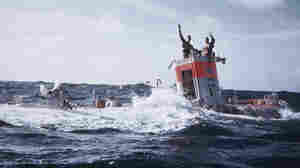 Navy Lt. Don Walsh (right) and Jacques Piccard wave after emerging from the Mariana Trench.