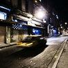 A taxi on a dark street.