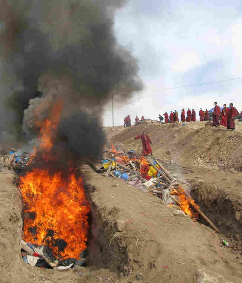 Tibetan Buddhist monks light a funeral pyre