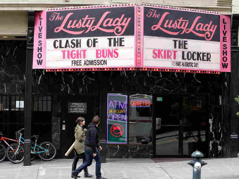 Pedestrians walk past the iconic marquee of The Lusty Lady in downtown Seattle.