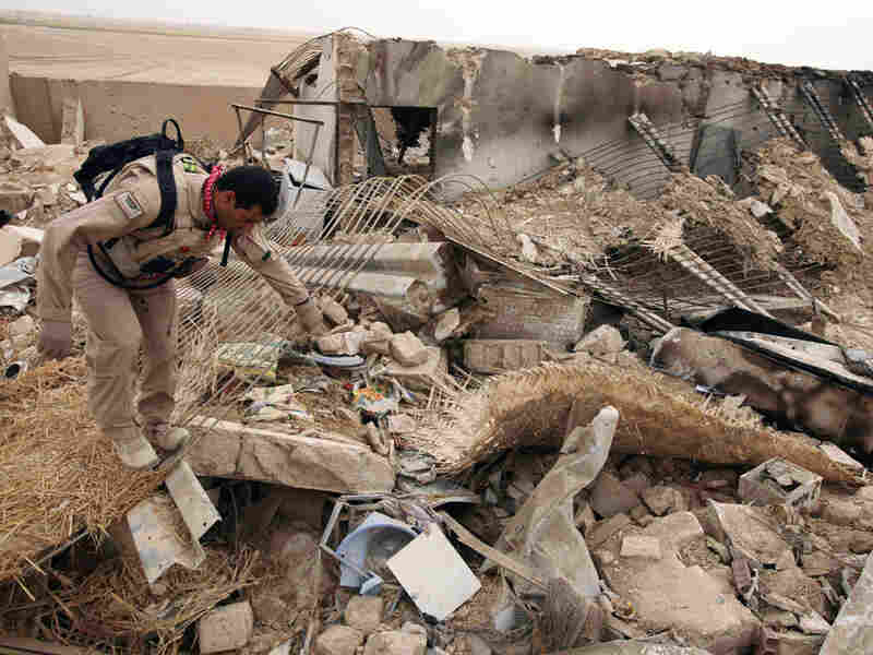 An Iraqi soldier combs through the site of a joint U.S-Iraqi raid that killed Baghdadi and Masri