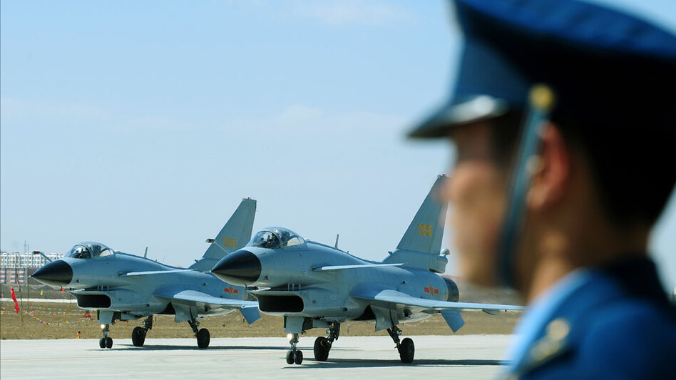 Chinese J-10 fighter jets pass an air force officer on the tarmac at the Yangcun airbase of the People's Liberation Army Air Force in Tianjin, southeast of Beijing, April 13, 2010.