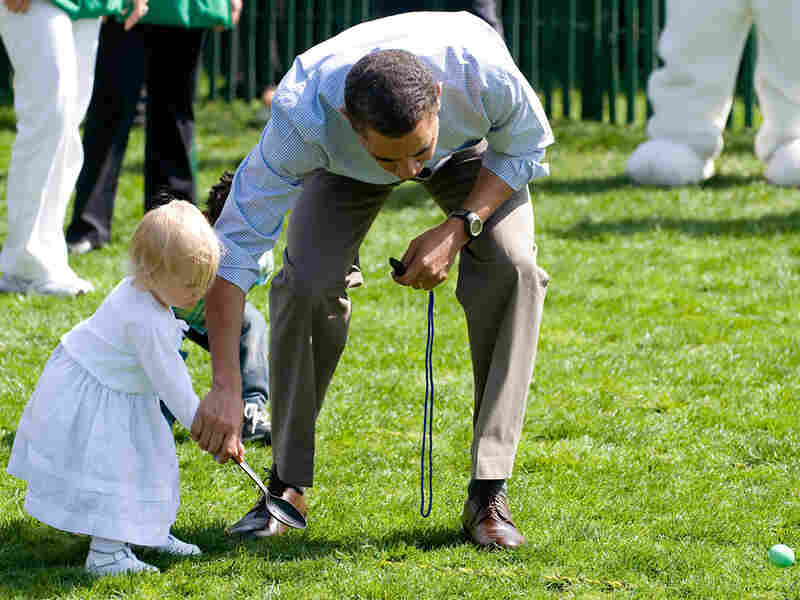 President Obama helps Lilian Plouffe with her egg during the White House Egg Roll.