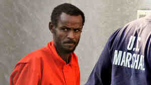 A suspected pirate from Somalia looks around as he is escorted into federal court