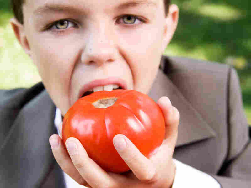 A boy eathing a tomato. iStockphoto.com