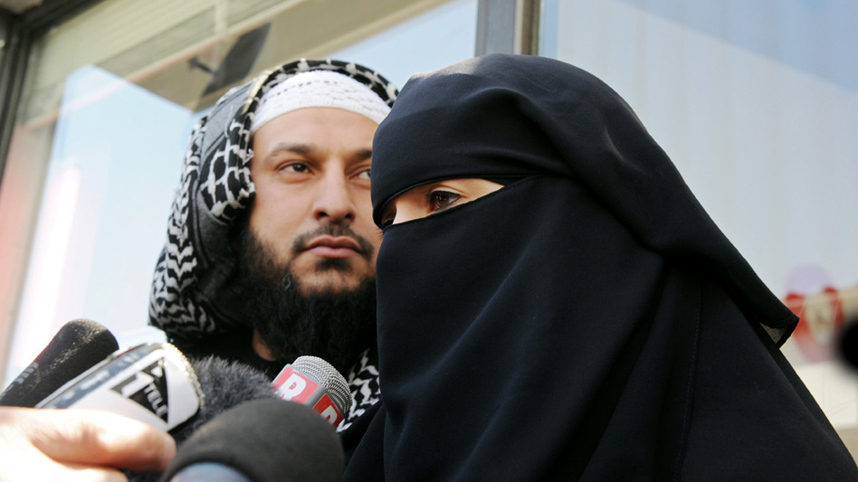 Lies Hebbadj and his wife, who was cited for driving her car while dressed in a full face-covering Islamic veil, talk to reporters on Friday. The government later alleged that Hebbadj is a polygamist with four wives.