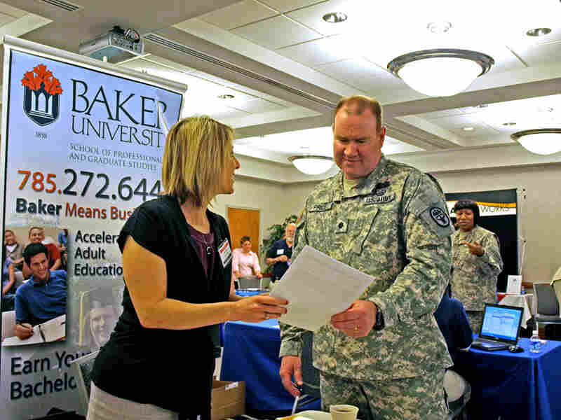 A representative from Baker University and Lt. Col. Andy Price review a resume.