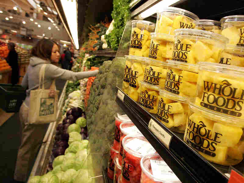 A customer shops for produce at a Whole Foods