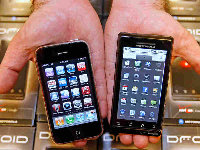 A manager holds an Apple iPhone and Motorola's Droid smart phone