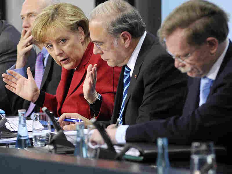 German Chancellor Angela Merkel (left) addresses a press conference about the European debt crisis.