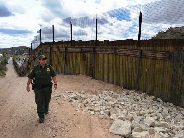 A U.S. Border Patrol officer keeps watch over the fence that divides the U.S. from Mexico in the town of Nogales, Ariz., on April 22. Mexico has denounced a newly passed Arizona law that requires police to question suspected illegal immigrants and orders people to carry proof of their immigration status.