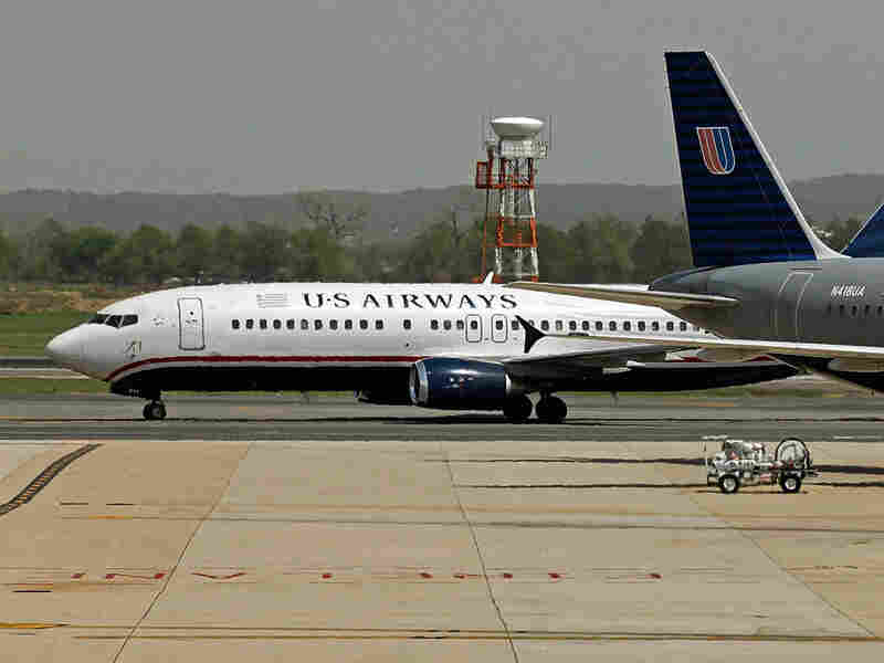 Airplanes belonging to U.S. Airways and United Airlines stand parked at their gates.