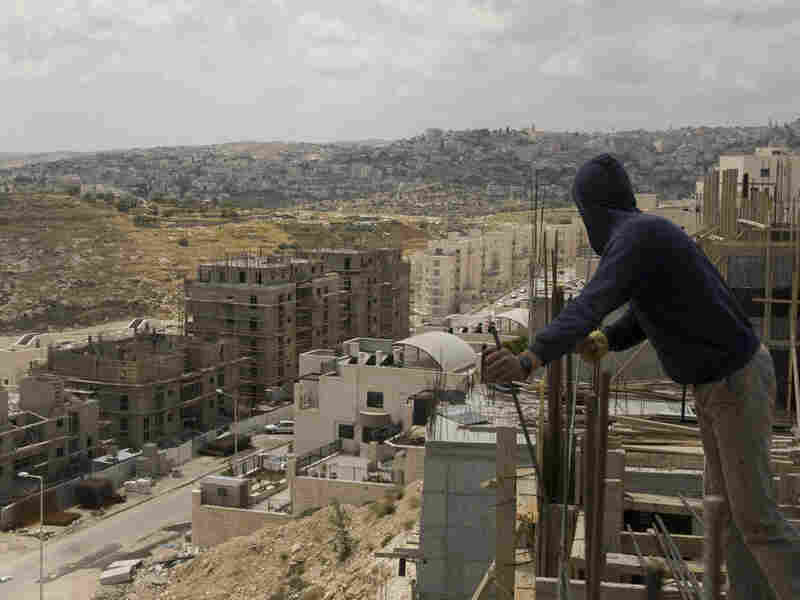 Palestinian laborers work on a new housing project in East Jerusalem